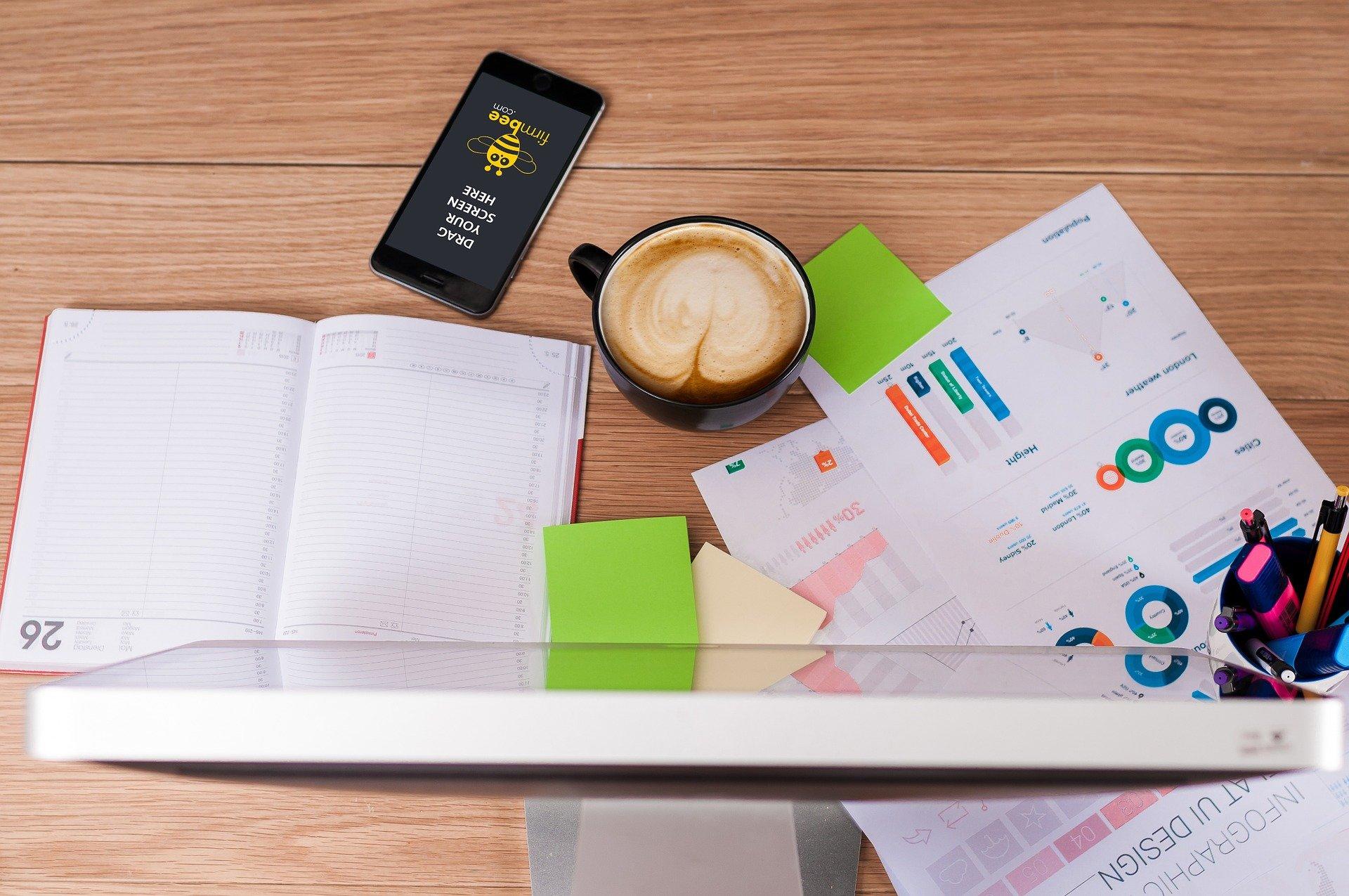 Tisch von oben, mit Computerbildschirm, Smartphone, Tasse Cappuccino, Blättern und Notizzetteln