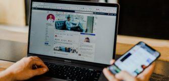 Auf dem Bild ist ein Laptop auf dem ein Facebookprofil zu sehen ist und ein Handy in der Hand daneben