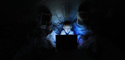 Kleinkind im Elternbett schaut auf einen hell leuchtenden Computer-Bildschirm