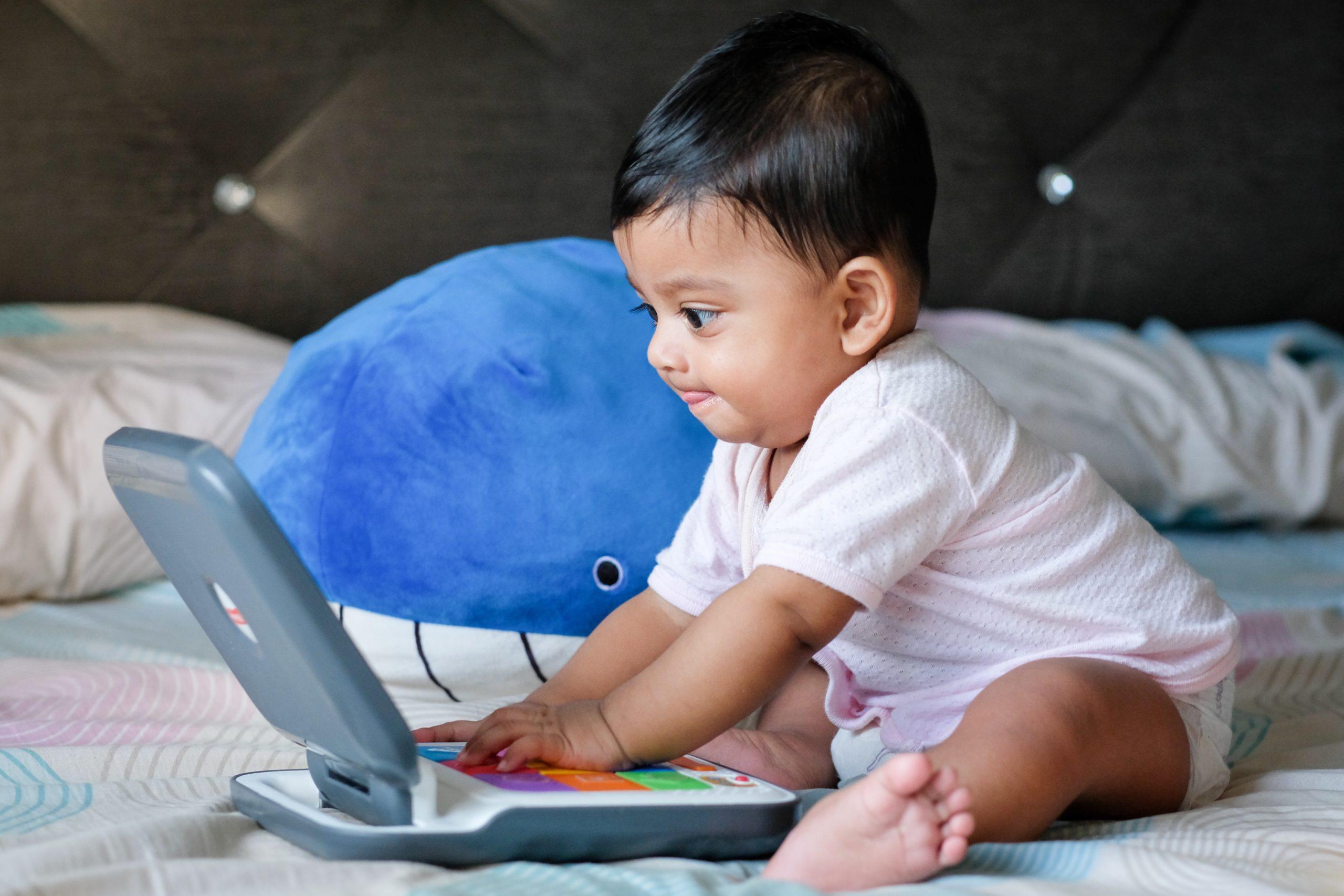 Kleinkind sitzend auf dem Bett spielt mit einem Kindercomputer