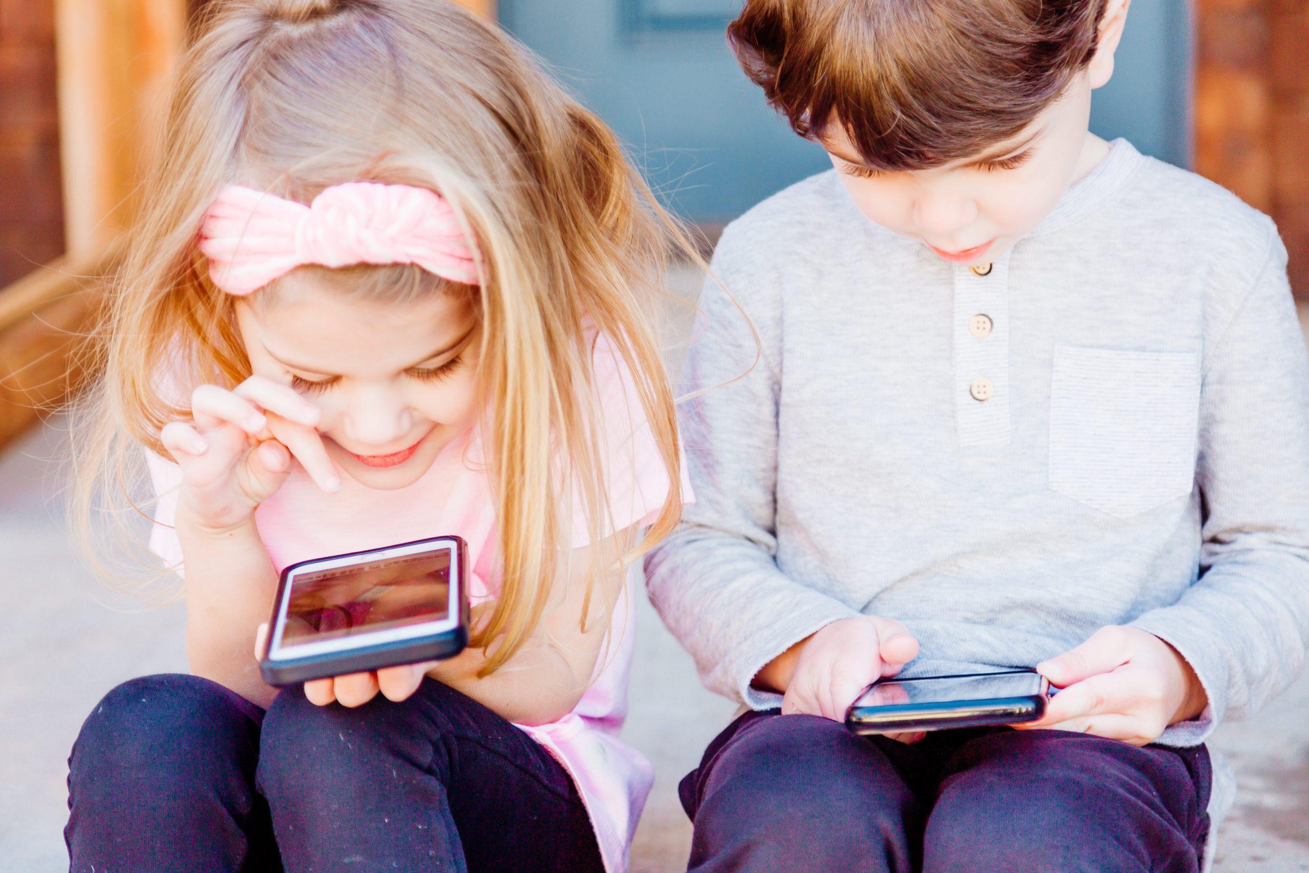 Ein kleines Mädchen und ein kleiner Junge schauen jeweils auf ein Handy in ihren Händen.