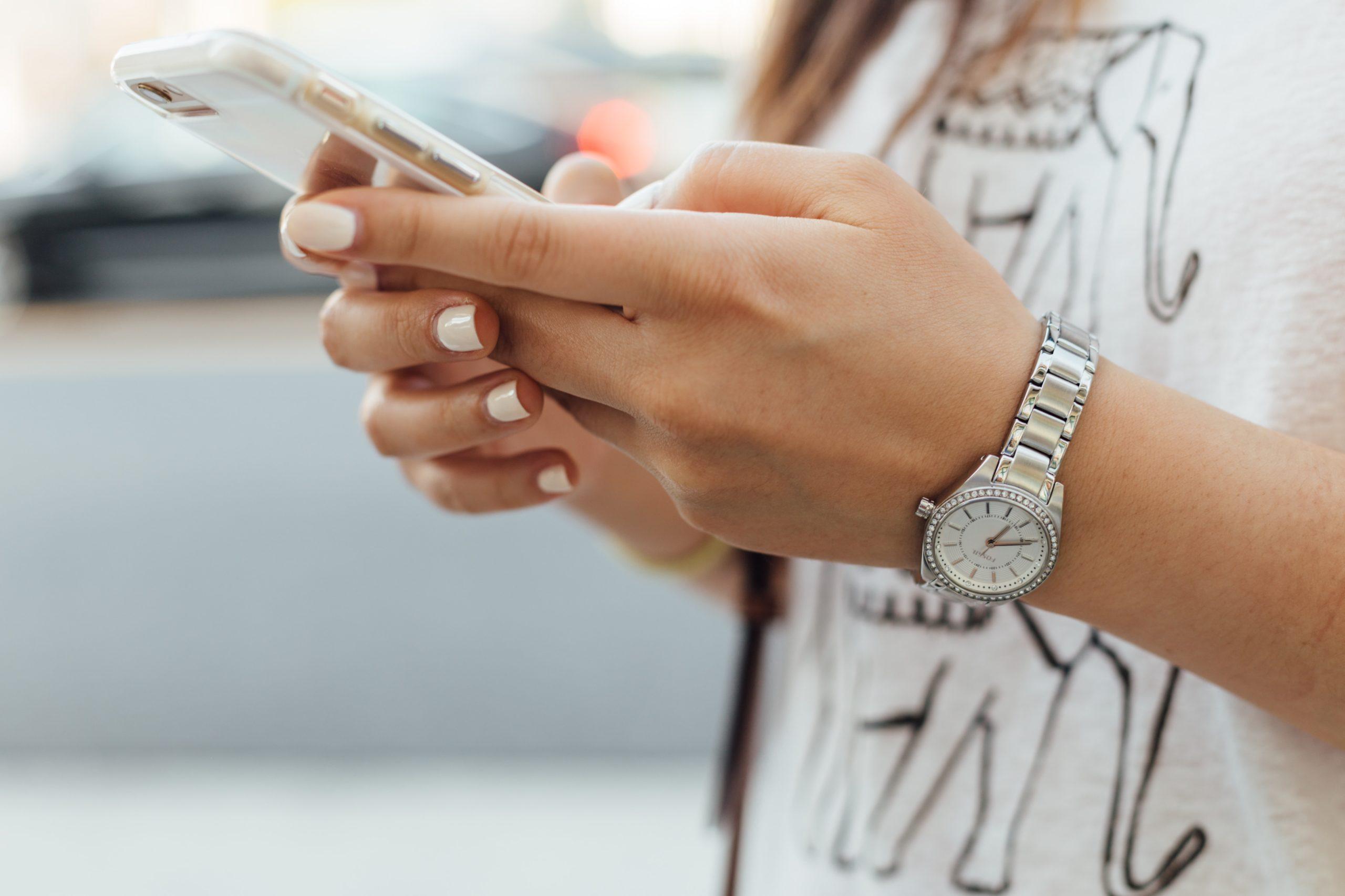 Hände einer jungen Frau, die auf einem Handy tippt